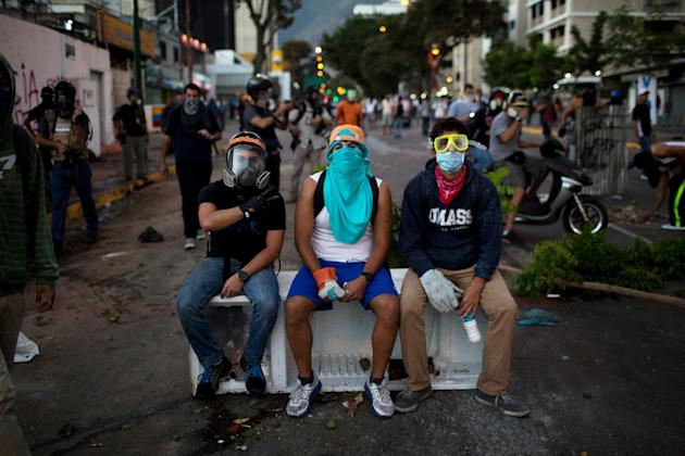 In this March 2, 2014 photo, anti-government demonstrators take a break on an old refrigerator used to build a barricade during clashes with security forces in Caracas, Venezuela. Fashion is not forei