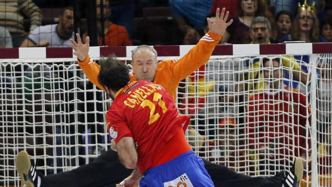 Canellas of Spain scores against goalkeeper Omeyer of France during their semi-final match of the 24th Men's Handball World Championship in Doha