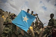 Soldiers of the Somali National Army display the Somali national flag upon their arrival in Saa'moja near Kismayo in this photo provided by the African Union-United Nations Information Support Team. Kenyan troops from the African Union force in Somalia entered Kismayo for the first time Monday, witnesses said, three days after launching a beach assault that led Islamist insurgents to withdraw