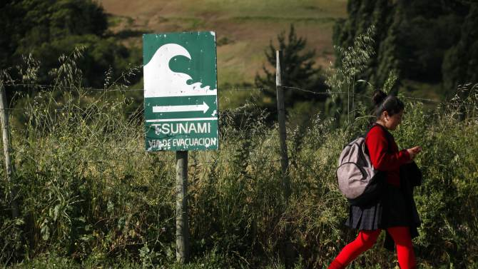 In this photo taken Nov. 29, 2012, a student walks past a sign indicating an evacuation route in the event of a tsunami, in Navidad, Chile. The road to the town of Navidad (Christmas in Spanish) is lined by a forest of eucalyptus trees and wildflowers that grow around painted tsunami warning signs that urge residents to build their homes high or dash for higher ground in case of a quake. (AP Photo/Luis Hidalgo)