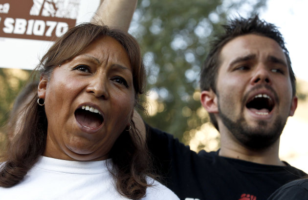 Maria Cruz, left, and Lincoln Statler chant as they join dozens who rally in front of  U.S. Immigration and Customs Enforcement building, a day after a portion of Arizona's immigration law took effect