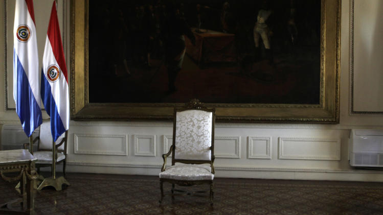 The presidential chair sits empty before the start of a news conference by Paraguay's new President Federico Franco at the presidential palace in Asuncion, Paraguay, Saturday, June 23, 2012. Former President Fernando Lugo's ouster by lawmakers on Friday has been widely condemned in Latin America as Franco is promising to honor foreign commitments and reach out to Latin American leaders to try to keep his country from becoming a regional pariah. (AP Photo/Jorge Saenz)
