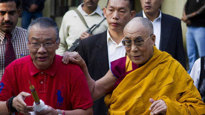 Tibetan spiritual leader the Dalai Lama, right, arrives to give a religious talk at the Tsuglakhang temple in Dharmsala, India, Tuesday, Oct. 4, 2011. The Dalai Lama has called off a visit to South Africa because he does not expect to get a visa, the Tibetan spiritual and political leader's office said Tuesday. (AP Photo/Ashwini Bhatia)
