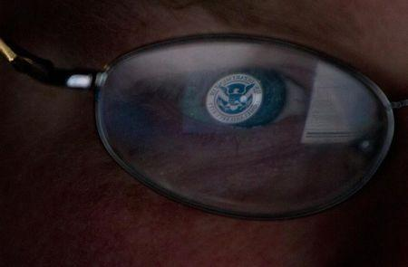 The logo of the U.S. Department of Homeland Security is reflected in the spectacles of an analyst working in a watch and warning center of a cyber security defense lab at the Idaho National Laboratory