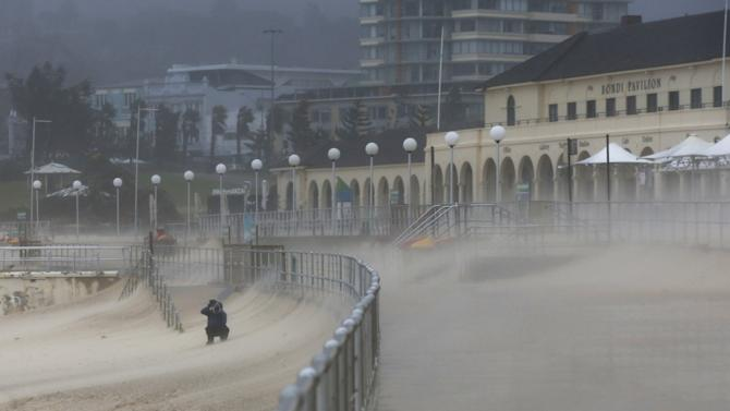 A man takes a picture of Bondi Beach's sand as heavy winds blow it inland