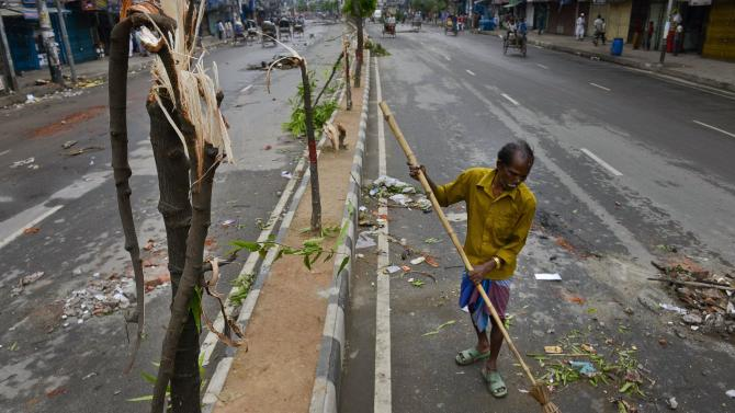 A cleaner sweeps a street after clashes between Bangladesh police and Islamic hardliners during a protest in Savar near Dhaka, Bangladesh, Monday, May 6, 2013. At least 15 people died in clashes Monday in Bangladesh, between police and Islamic hardliners demanding that Bangladesh implement an anti-blasphemy law, police said. (AP Photo/Ismail Ferdous)