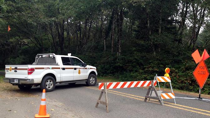 """A road block closes access to Bastendorf Beach outside Coos Bay, Ore., on Tuesday, Aug. 19, 2014, where authorities say a drive-by gunman shot five vehicles, killing a Michigan man as he slept, then shot and killed himself. Authorities say they have reason to believe the gunman, Zachary Levi Brimhall, 34, of Dillard, Ore., may also have """"done harm"""" to his father, whose vehicle was found in another rural area of Coos County. The investigation was slowed by the discovery of explosives in Brimhall's vehicle. (AP Photo/Angelica Carrillo/KCBY)"""