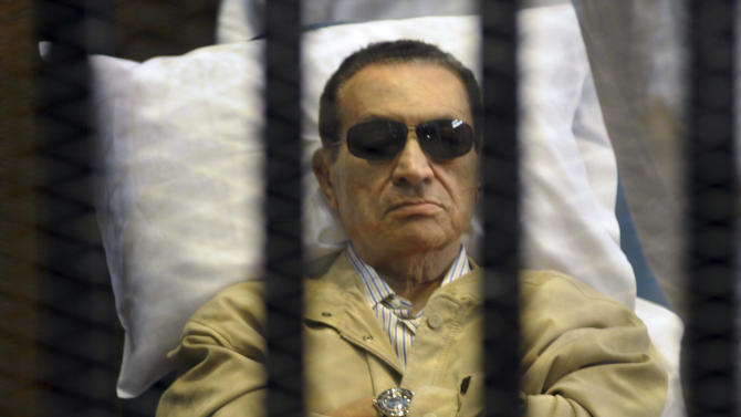 FOR USE AS DESIRED, YEAR END PHOTOS - FILE - In this June 2, 2012 file photo, Egypt's ex-President Hosni Mubarak lays on a gurney inside a barred cage in the police academy courthouse in Cairo, Egypt. Mubarak was sentenced to life in prison for his role in the killing of protesters during last year's revolution that forced him from power, a verdict that caps a stunning fall from grace for a man who ruled the country as his personal fiefdom for nearly three decades.(AP Photo/File)