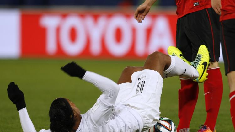 Ronaldinho of Brazil's Atletico Mineiro hits the leg of Zhao Xuri of China's Guangzhou Evergrande during their 2013 FIFA Club World Cup third place soccer match in Marrakech stadium