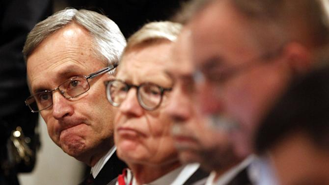 "FILE - In this March 8, 2011 file photo, Ohio State football coach Jim Tressel, left, and university President E. Gordon Gee, second from left, listen as athletic director Gene Smith speaks during a news conference in Columbus, Ohio. As the country absorbs the independent report released Thursday, July 12, 2012, on the Penn State sex abuse scandal, some see it as more than an indictment of one school. They see it as underscoring how major-college sports, football in particular, have run amok. When Gee heard Tressel concede he had reason to believe several star players were taking money and free tattoos from a suspected drug dealer and yet he had told no one, Gee was asked if he had considered firing Tressel. ""Let me just be very clear,"" Gee said with a grin, ""I'm just hopeful the coach doesn't dismiss me."" The joke fell flat, but echoed around the country. It confirmed what many already believed about the balance of power in college sports today: some football teams run universities, not the other way around. (AP Photo/Terry Gilliam, File)"