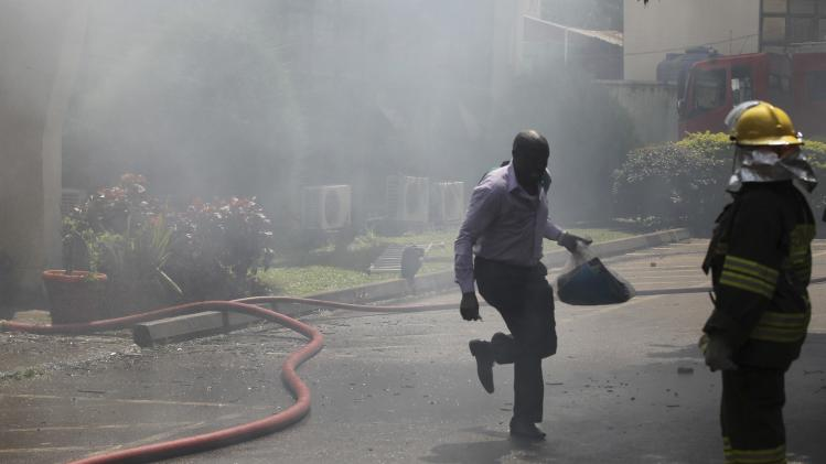Man runs out of a building carrying documents in a bag, as a fire rages on at headquarters of the Nigeria Football Federation in Abuja