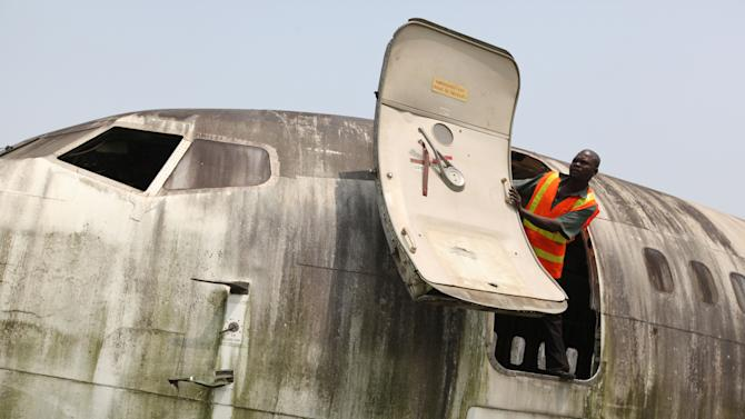 A worker looks out from the fuselage of an abandoned aircraft at Murtala Muhammed International Airport in Lagos, Nigeria, Thursday, Jan. 31, 2013. Nigerian aviation officials have begun trying to dismantle and remove the hulks of abandoned airplanes from airports around the country. Officials say there are least 65 abandoned planes at the country's airports, with at least 13 at Lagos' international airport. (AP Photo/Jon Gambrell)