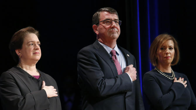 Defense Secretary Carter stands between Supreme Court Justice Kagan and wife Stephanie during a ceremonial swearing in ceremony at the Pentagon in Washington