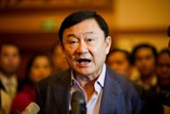 "Former Thai Prime Minister Thaksin Shinawatra speaks to journalists as he arrives at a hotel in Vientiane, the capital of Laos. Thaksin told his ""Red Shirt"" supporters Wednesday that he expects to set foot in his homeland again this year"