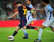 Barcelona&#39;s forward Lionel Messi (L) shoots to score during their Spanish league football match against Granada at the Camp Nou stadium in Barcelona. Barcelona won 2-0