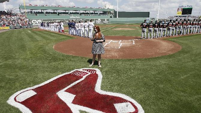 Alyssa Hall of Fort Myers, Fla., sings the national anthem as the Miami Marlins and Boston Red Sox line the base lines before a interleague spring training baseball game in Fort Myers Fla., March 6, 2015. (AP Photo/Tony Gutierrez)