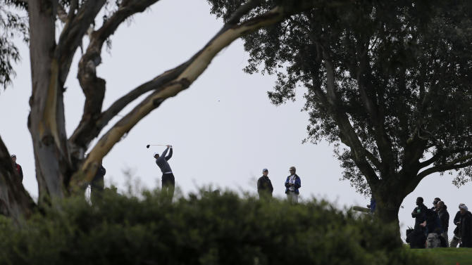 Tiger Woods drives from behind the trees on the south hole of the South Course at Torrey Pines during the third round of the Farmers Insurance Open golf PGA tournament Sunday, Jan. 27, 2013, in San Diego. (AP Photo/Lenny Ignelzi)