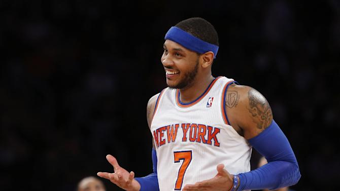 "In this Feb. 24, 2014, file photo, New York Knicks' Carmelo Anthony (7) smiles after hitting a 3-point shot against the Dallas Mavericks during an NBA basketball gam in New York. Anthony is remaining with the Knicks, saying he wants ""to stay and build here with this city and my team."" Anthony made his decision official Sunday with a posting on his website. He writes: ""In the end, I am a New York Knick at heart."""