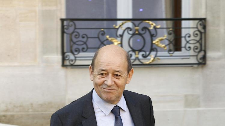 French Defense Minister Jean Yves Le Drian gestures toward reporters as he leaves the Elysee Palace following a Defense meeting with French President Francois Hollande, in Paris, Wednesday Jan 16, 2013.(AP Photo/Remy de la Mauviniere)