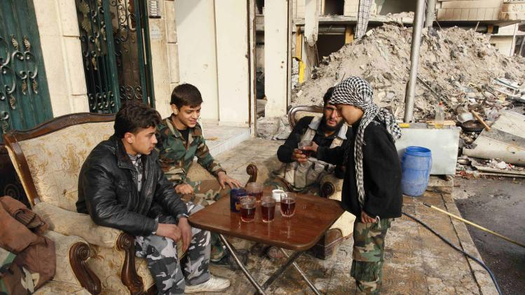 File picture shows Hasan, an 11-year-old fighter in the Free Syrian Army, distributing tea to his fellow fighters at Aleppo's Karm al-Jabal district
