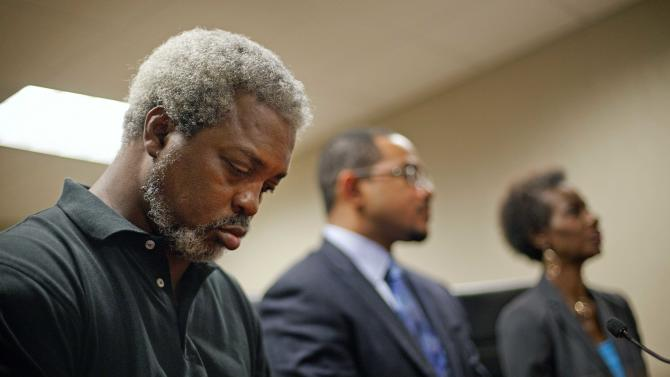 Robert Champion, Sr., left, the father of Florida A&M University drum major Robert Champion who died in a hazing incident, listens during a news conference with wife Pam Champion, right, and attorney Chris Chestnut, following yesterday's announcement of charges in his son's death Thursday, May 3, 2012, in Atlanta. Pam Champion, the mother of Robert Champion, said Thursday that the only way to halt hazing in the program is to disband the marching band until further notice. Her comment come a day after 13 people were charged in her son's death. (AP Photo/David Goldman)