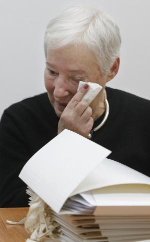 A daughter of Yiddish writer Naftali Herts Kon, Ina Lancman wipes her face as she reads in the file folders holding Kon's writings that were returned to the daughters and to the Warsaw City Archives Tuesday, March 5, 2013. The letters, newspaper articles and poems by Naftali Herts Kon, whose real name was Jakub Serf, were deposited with the City of Warsaw Archives by communist authorities after he was sentenced to prison on fabricated charges, in 1963. After 15 months in confinement, Kon left for Israel where he died in 1971. (AP Photo/Czarek Sokolowski)