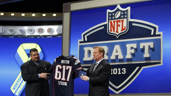 Retired New England Patriots' Joe Andruzzi and NFL Commissioner Roger Goodell honor the victims and first responders of the Boston Marathon bombings during the first round of the NFL football draft, Thursday, April 25, 2013, at Radio City Music Hall in New York. (AP Photo/Jason DeCrow)
