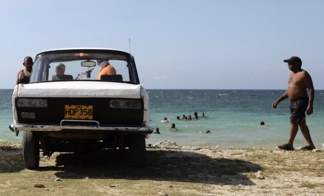 A man walks near a parked car beside the sea on the outskirts of Havana
