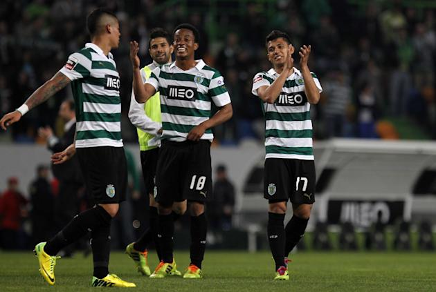 Sporting's Freddy Montero, right, from Colombia, Andre Carrillo, center, from Peru, and Marcos Rojo, from Argentina, celebrate at the end of the Portuguese league soccer match between Sporting and