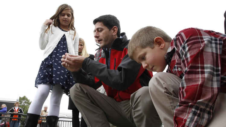 Republican vice presidential candidate, Rep. Paul Ryan, R-Wis., talks to his daughter, Liza, and son, Sam, about the stadium astroturf at a Bowling Green State University and Miami University of Ohio football game, Saturday, Oct. 13, 2012 in Bowling Green, Ohio. (AP Photo/Mary Altaffer)
