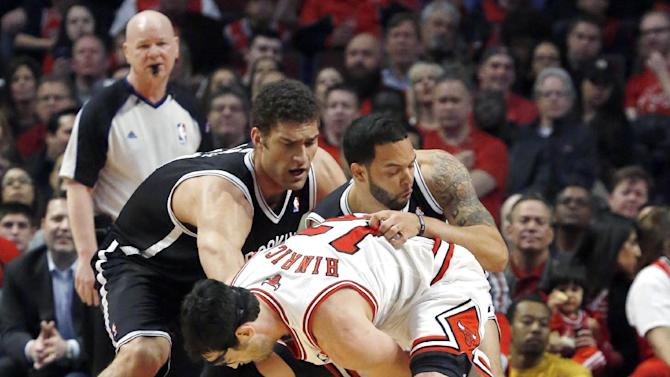 Brooklyn Nets center Brook Lopez, left, and point guard Deron Williams, right, battle Chicago Bulls shooting guard Kirk Hinrich for a loose ball during the first half of Game 3 of their first-round NBA basketball playoff series, Thursday, April 25, 2013, in Chicago. (AP Photo/Charles Rex Arbogast)