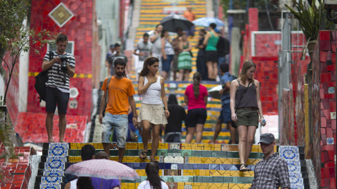"""People walk up and down a stairway that was decorated by Chilean artist Jorge Selaron, which he titled the """"Selaron Stairway"""" in Rio de Janeiro, Brazil, Thursday, Jan. 10, 2013. Selaron, an eccentric Chilean artist and longtime Rio resident who created a massive, colorful tile stairway in the bohemian Lapa district that's popular with tourists, was found dead on the stairway on Thursday. He was 54. Authorities are investigating the cause of death. (AP Photo/Felipe Dana)"""
