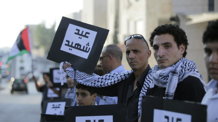 "Jordanian and Palestinian protesters carry placards that read in Arabic: ""Eid Martyr"" during a protest against the Israeli war on Gaza, in Amman, Jordan, Monday July 28, 2014. Tens of protesters gathered near the Israeli embassy in a silent protest on the first day of Eid al-Fitr, to protest the Israeli bombing of Gaza. (AP Photo/Mohammad Hannon)"