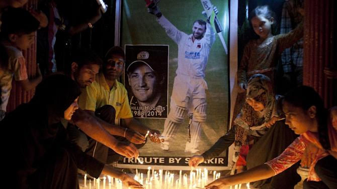 Pakistani cricket fans light candles to pay tribute to Australian cricketer Phillip Hughes in Karachi, Pakistan, Thursday, Nov. 27, 2014. Test batsman Hughes died in a Sydney hospital on Thursday, Nov. 27, two days after being struck on the head by a cricket ball during a domestic first-class match. He was 25. (AP Photo/Shakil Adil)