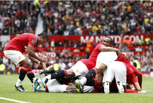 Manchester United's Wayne Rooney not pictured celebrates with team mates after he scored a goal against Arsenal during their English Premier League soccer match at Old Trafford, Manchester, England, Sunday Aug. 28, 2011. (AP Photo/Jon Super)