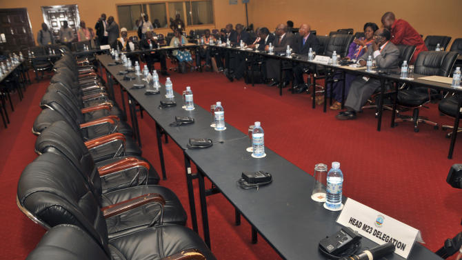 The Congolese government delegation, right, sits opposite a row of empty seats intended for the delegation of Congolese M23 rebels, who did not turn up for the crucial meeting, at peace talks being held in Kampala, Uganda Monday, Dec. 10, 2012. Representatives of rebels attending peace talks with the Congolese government dodged a crucial meeting Monday at which the government delegation was to respond to earlier criticism, a development that could jeopardize negotiations to end the crisis in eastern Congo. (AP Photo/Stephen Wandera)