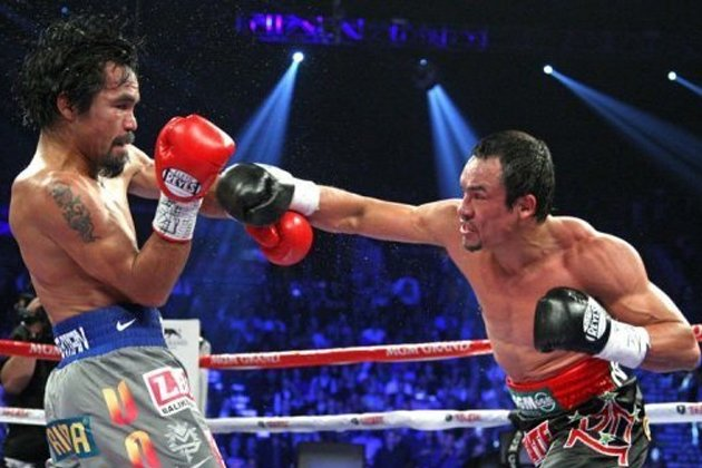 Manny Pacquiao (L) and Juan Manuel Marquez battle during their welterweight fight at the MGM Grand Garden in Las Vegas, Nevada. Marquez knocked out Pacquiao in the 6th round. Pacquiao says he welcomes another fight with Marquez, one that would put them into an elite class of boxing champions. (AFP)
