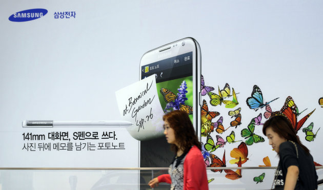 Visitors walk by a billboard of Samsung Electronics&#39;s product at a showroom of its headquarters in Seoul, South Korea, Friday, Oct. 5, 2012. Samsung Electronics Co. tipped all-time high quarterly operating profit, likely driven by strong sales of high-end smartphones that offset weak semiconductor orders. (AP Photo/Lee Jin-man)