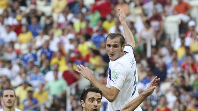Spain's Xavi Hernandez, left, and Italy's Giorgio Chiellini challenge for the ball during the soccer Confederations Cup semifinal match between Spain and Italy at Castelao stadium in Fortaleza, Brazil, Thursday, June 27, 2013. (AP Photo/Antonio Calanni)