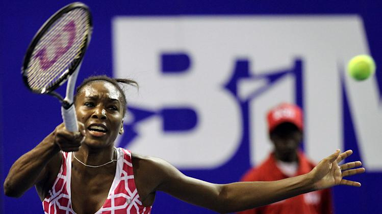 Venus Williams of the U.S. returns a service from sister Serena during an exhibition tennis match at Ellis Park Indoor Arena in Johannesburg, South Africa, Sunday, Nov. 4, 2012. (AP Photo/Themba Hadebe)