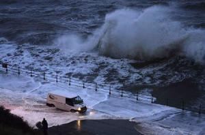 A van drives through seawater washed onto the promenade of the north bay in Scarborough, northern England