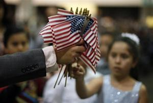A man hands out U.S. flags at a naturalization ceremony for new U.S. citizens in Los Angeles