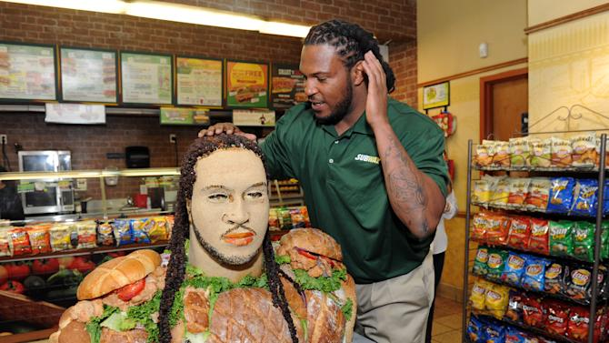 """IMAGE DISTRIBUTED FOR SUBWAY - Linebacker Jarvis Jones, 2013 draft prospect and newest Famous Fan of SUBWAY, admires his hair on the life-size """"Smokehouse BBQ Chicken"""" sculpture to announce Jones' official SUBWAY Famous Fan title, Tuesday, April 23, 2013, in New York.  The sculpture is an artistic representation of the football star from the chest up, standing approximately three feet tall and made of almost entirely SUBWAY Smokehouse BBQ Chicken.  Jarvis joins a roster of fellow Famous Fans that include Robert Griffin III, Justin Tuck, Michael Strahan, Blake Griffin and Michael Phelps.† (Photo by Diane Bondareff/Invision for SUBWAY/AP Images)"""