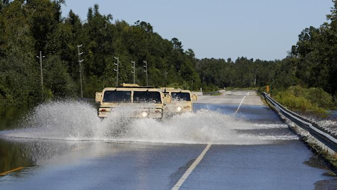 National Guard humvees plow through flood waters on Highway 377 near Kingstree, S.C., Wednesday, Oct. 7, 2015.  (AP Photo/Mic Smith)