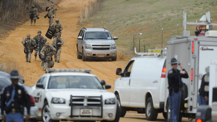 "FILE - In this Jan. 30, 2013 file photo, heavily armed men move away from the home of Jimmy Lee Dykes in Midland City, Ala., where he is holding a 5-year-old boy hostage after kidnapping him from a school bus the day before. The boy's mother told Dr. Phil McGraw in an interview to be aired on the ""Dr. Phil Show"" on Wednesday, Feb. 13, that her son saw FBI says agents fatally shoot Dykes when they rescued the boy. (AP Photo/Montgomery Advertiser, Mickey Welsh, File)  NO SALES"