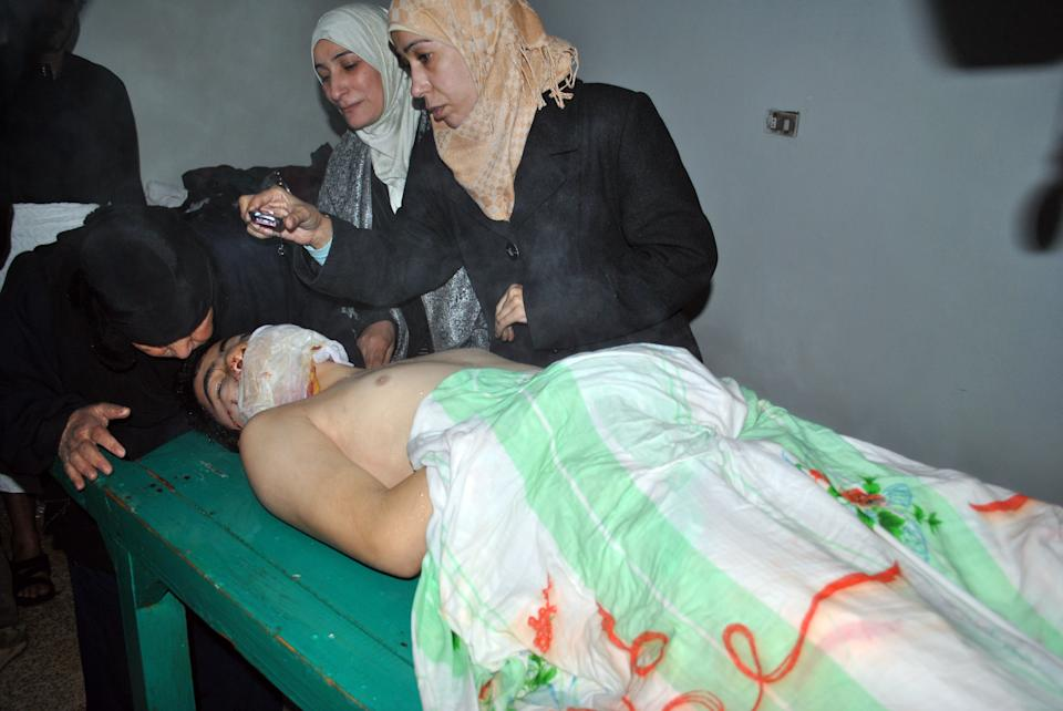 In this Tuesday Feb. 7, 2012 photo,  a Syrian woman, left, mourns over the body of a man who witnesses say was killed by Syrian government forces shelling, in the Rastan neighborhood of Homs province, central Syria. (AP Photo)
