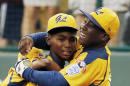 FILE - In this Aug. 23, 2014 file photo, Chicago's Joshua Houston, right, celebrates with Ed Howard after their 7-5 win in the U.S. final game against Las Vegas at the Little League World Series baseball tournament in South Williamsport, Pa. The team won the U.S. title, but lost 8-4 to South Korea in the championship game. The team united the city of Chicago and will be feted with a parade Wednesday, Aug. 27. (AP Photo/Gene J. Puskar, File)