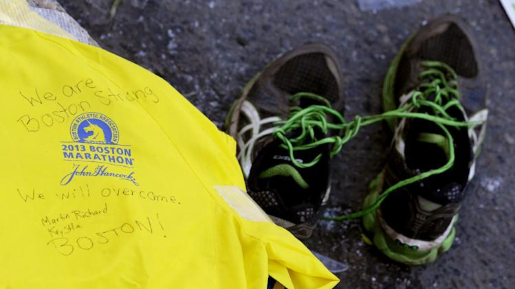 A message is written on a volunteer's jacket near running shoes at a makeshift memorial on Boylston Street near the blast site of the Boston Marathon explosions, Thursday, April 18, 2013, in Boston. The city continues to cope following Monday's explosions near the finish line of the marathon. (AP Photo/Julio Cortez)