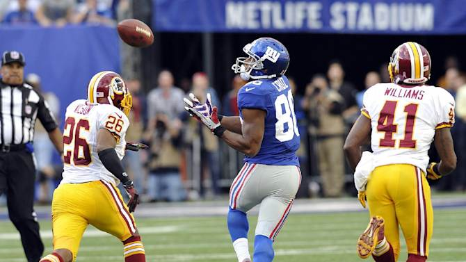 New York Giants wide receiver Victor Cruz (80) catches a pass as Washington Redskins cornerback Josh Wilson (26) and Madieu Williams pursue him during the second half of an NFL football game on Sunday, Oct. 21, 2012, in East Rutherford, N.J. The Giants won the game 27-23. (AP Photo/Bill Kostroun)