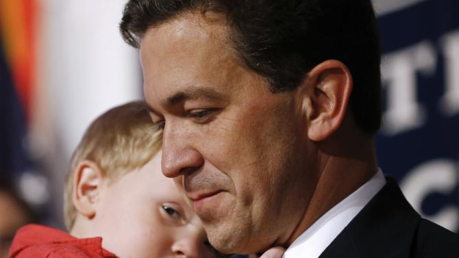 McDaniel holds his son, Chamberlain, after he delivered a concession speech in Hattiesburg
